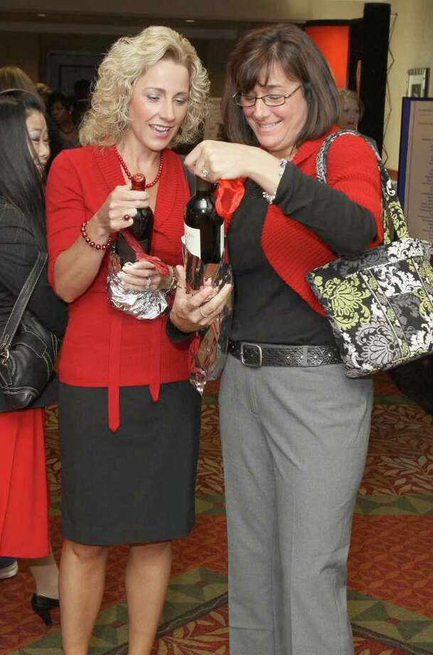 Tina Trifaro (left) and Eileen Rogers(right) check to see what wine they chose from the wine pull during the 7th Annual Go Red For Women Luncheon on May 18, 2011, in Troy to benefit the American Heart Association.  (Photo by Joe Putrock/Special to the Times Union) Photo: Joe Putrock / Joe Putrock