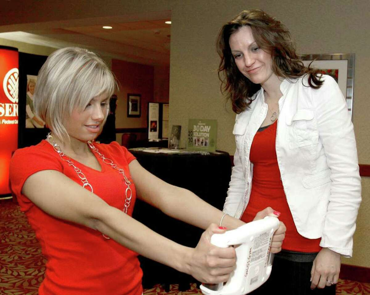 Troy, NY - May 18, 2011 - (Photo by Joe Putrock/Special to the Times Union) - Gold's Gym Marketing Coordinator Charlotte Todd(right) helps Angela Rainbolt(left) though a body fat test during the 7th Annual Go Red For Women Luncheon to benefit the American Heart Association.