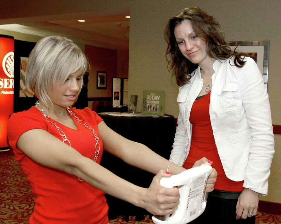 Troy, NY - May 18, 2011 - (Photo by Joe Putrock/Special to the Times Union) - Gold's Gym Marketing Coordinator Charlotte Todd(right) helps Angela Rainbolt(left) though a body fat test during the 7th Annual Go Red For Women Luncheon to benefit the American Heart Association. Photo: Joe Putrock / Joe Putrock