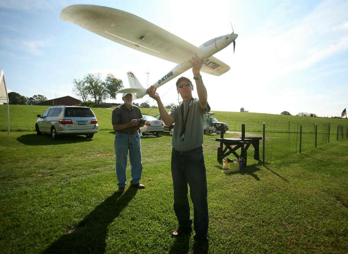 Julian Greenberger, left of Stratford, and Ed Martin of Shelton launch a powered styrofoam glider at the White Hills Eagles Remote Control Airplane Club flying field on the Stern Farm on Birdseye Road in Shelton, Conn. on Thursday, September 24, 2009.