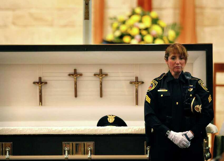 Standing in front of her husband's casket, Bexar County Sheriff Deputy Sgt. Yvonne Vann waits to greet fellow officers and friends before funeral services for Sgt. Kenneth Gary Vann.