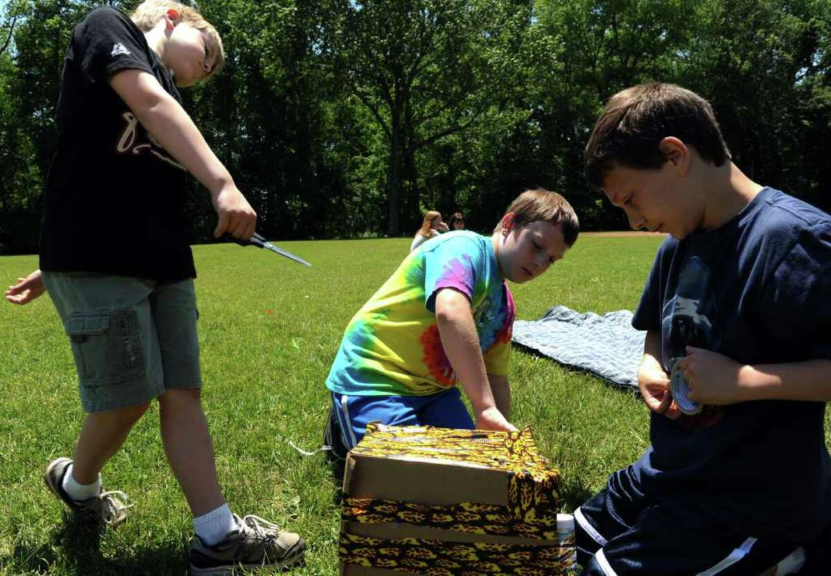"""Fifth graders Taylor Benoit, Michael Cooper and Andrew Marinelli, from left, conduct an """"eggs-periment"""" at Orchard Hills Elementary School in Milford, Conn. Friday, June 3, 2011. Eggs in student-designed carriers were dropped 100 feet from atop a firetruck's extended ladder."""