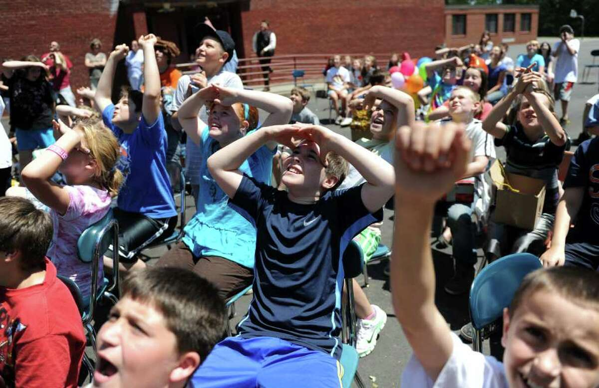 """Fifth graders conduct an """"eggs-periment"""" at Orchard Hills Elementary School in Milford, Conn. Friday, June 3, 2011. Eggs in student-designed carriers were dropped 100 feet from atop a firetruck's extended ladder."""