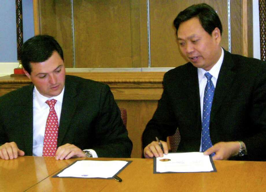 Yan Jun, Vice Mayor of Xinyi municipal People's government (Xinyi City, Jiangsu, China), and Timothy Herbst, first selectman of Trumbull, signing the memorandum of understanding in English and Chinese inside Trumbull Town Hall Friday, June 3rd, 2011. Photo: Monica Szakacs / Connecticut Post staff photo