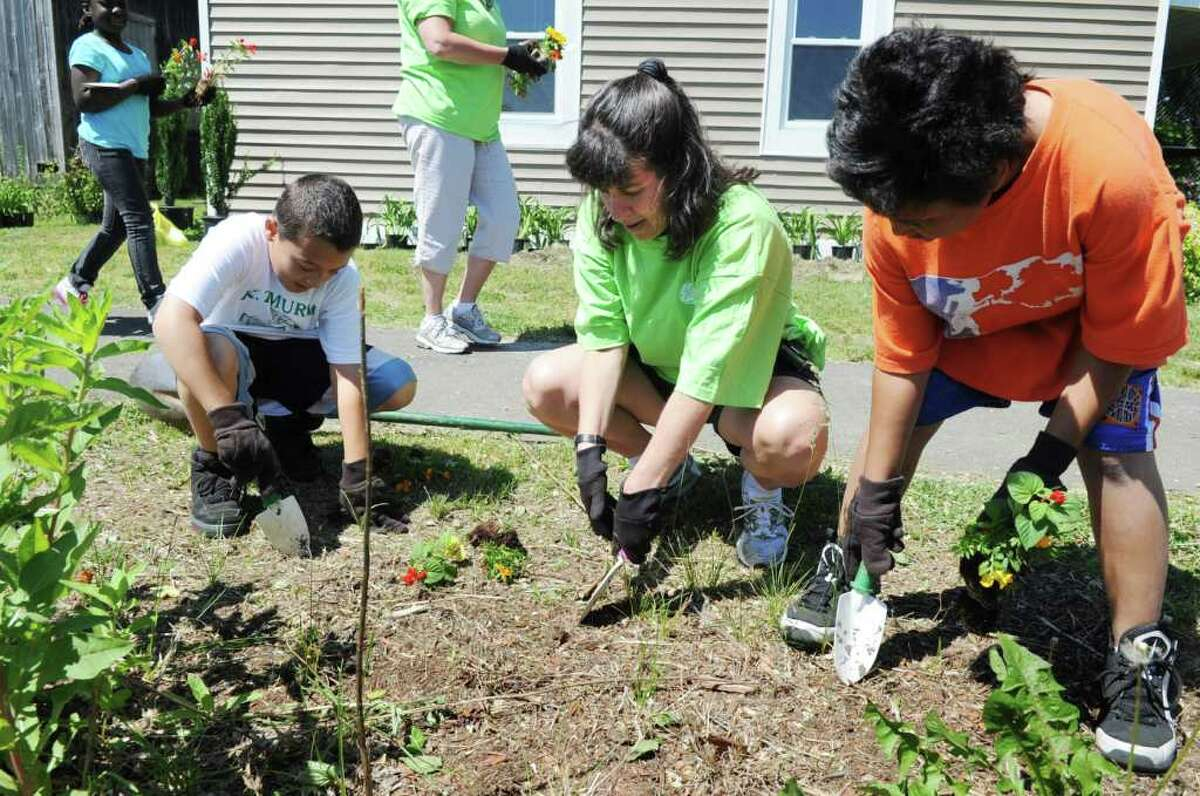 Dante Kelsey, 11, and Michael Tompkins, 10, work with Pam Green as students from KT Murphy Elementary School work side by side with their GE ePals during the 4th annual community service event. The group helped clean up and plant flowers at Cove Island Park in Stamford, Conn. on Friday June 3, 2011.