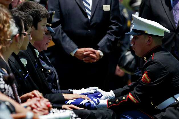 Lance Cpl. Hector Jaramillo, right, hands the American Flag to Bexar County Sheriff Deputy Sgt. Yvonne Vann, the wife of slain Bexar County Sheriff Deputy Sgt. Kenneth Gary Vann at St. Joseph Catholic Cemetery at Honey Creek in Spring Branch on Friday, June 3, 2011. LISA KRANTZ/lkrantz@express-news.net Photo: LISA KRANTZ, Express-News / SAN ANTONIO EXPRESS-NEWS
