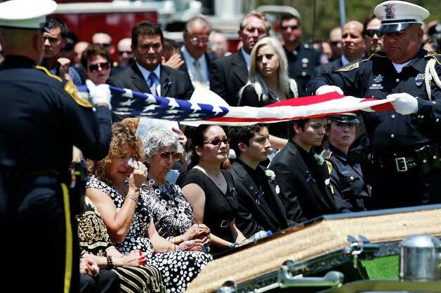 Family members of Bexar County Sheriff Deputy Sgt. Kenneth Gary Vann including, from left, his sister, Virginia Jimenez, his aunt, Rosalinda Keiser, his daughter, Rachael Vann, his sons Kenneth Vann, Jr. and Justin Vann and his wife, Bexar County Sheriff Deputy Sgt. Yvonne Vann watch as Bexar County Sheriff Honor Guard Deputies William Hendricks, left, and Raul Medellin, right, fold the flag covering Sgt. Vann's casket at St. Joseph Catholic Cemetery at Honey Creek in Spring Branch on Friday, June 3, 2011. LISA KRANTZ/lkrantz@express-news.net Photo: LISA KRANTZ, Express-News / SAN ANTONIO EXPRESS-NEWS