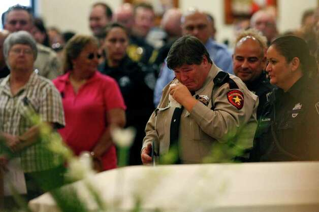 Nueces County Sheriff Deputy Margaret Davis, center, mourns next to Bexar County Sheriff Deputy Tillie Willborn, right, during the Funeral for Bexar County Sheriff Deputy Sgt. Kenneth Gary Vann at St. Joseph Catholic Church at Honey Creek in Spring Branch on Friday, June 3, 2011. LISA KRANTZ/lkrantz@express-news.net Photo: LISA KRANTZ, Express-News / SAN ANTONIO EXPRESS-NEWS