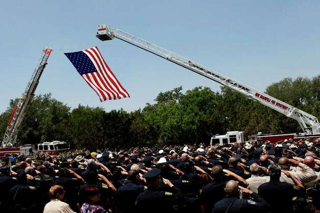 Law enforcement officers and other mourners salute as the casket of Bexar County Sheriff Deputy Sgt. Kenneth Gary Vann is taken to the gravesite at St. Joseph Catholic Cemetery at Honey Creek in Spring Branch on Friday, June 3, 2011. LISA KRANTZ/lkrantz@express-news.net Photo: LISA KRANTZ, Express-News / SAN ANTONIO EXPRESS-NEWS