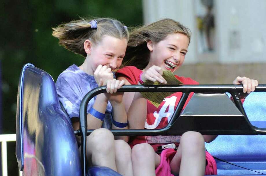 From left, Suzy Ryckman, 11, and Caroline Kelly, also 11, both of Riverside, react while riding a carnival ride during the St. Paul's Episcopal Church 70th annual Fair For All in Riverside, Friday night, June 3, 2011. Photo: Bob Luckey / Greenwich Time