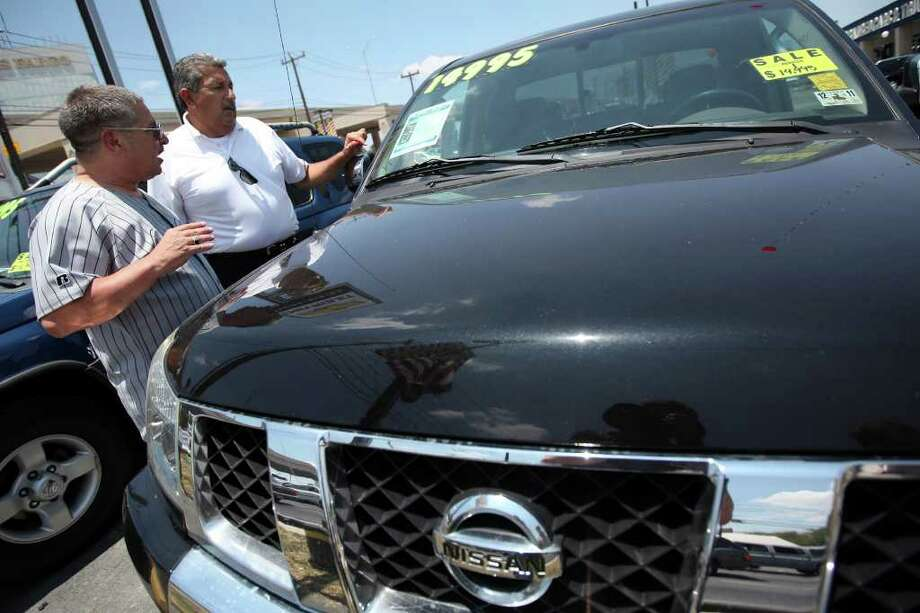Bandera resident Tony Dankowski, left, speaks with Ancira Chevrolet salesman Joe Idar about a used Nissan truck that he is interested in buying June 3, 2011. According to Ancira Kia general manager Jason Thompson, used car prices have hit their highest level in 16 years.  ANDREW BUCKLEY / abuckley@express-news.net Photo: ANDREW BUCKLEY, SAN ANTONIO EXPRESS-NEWS / SAN ANTONIO EXPRESS-NEWS