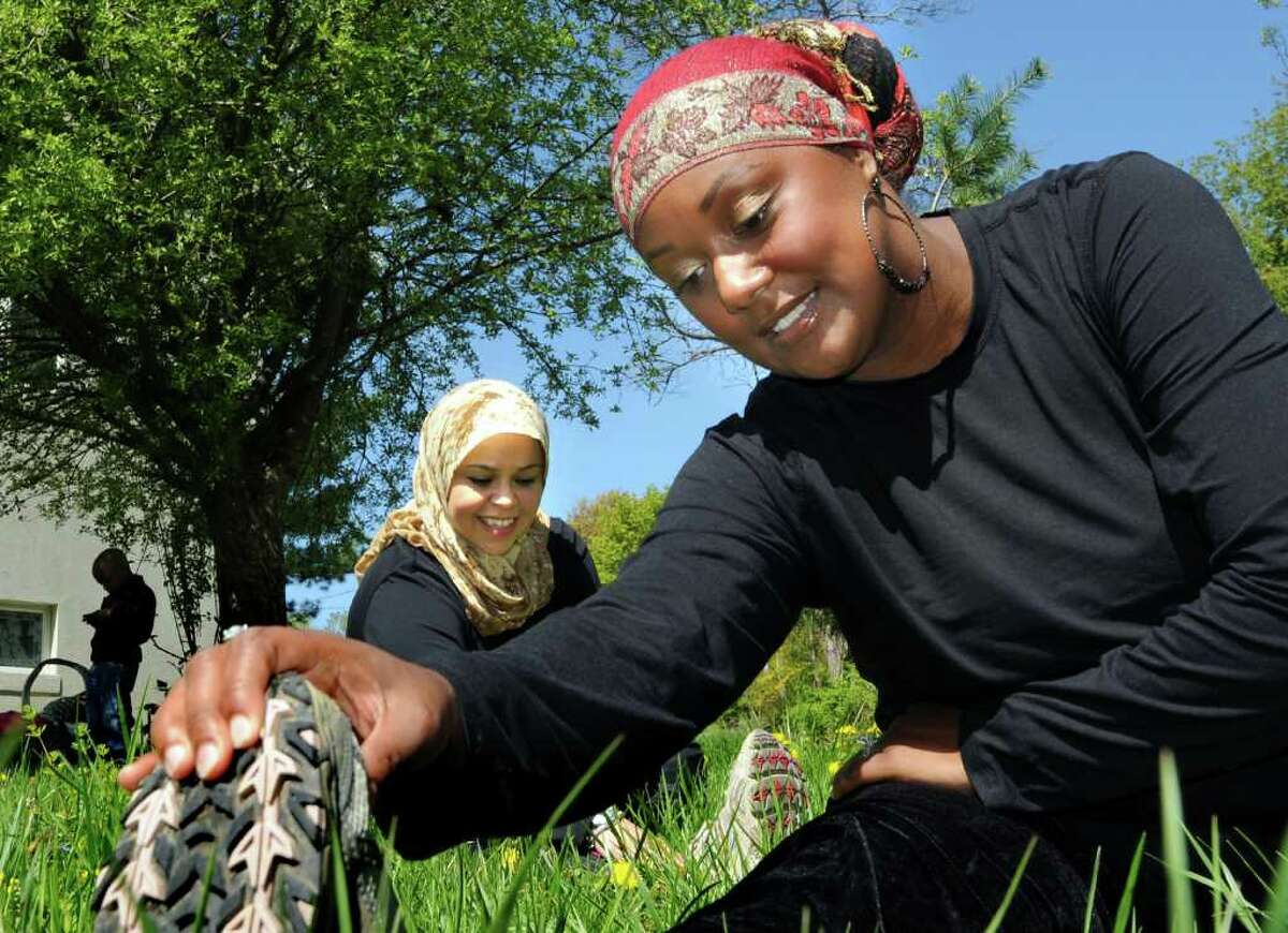 Lisa Jones of Niskayuna, center, and Anzala Alozie of Albany, right, stretch out on Tuesday, May 10, 2011, at the Islamic Center of the Capital District in Colonie, N.Y. Both of the Muslim women are training for the Freihofer's Run in June. (Cindy Schultz / Times Union)