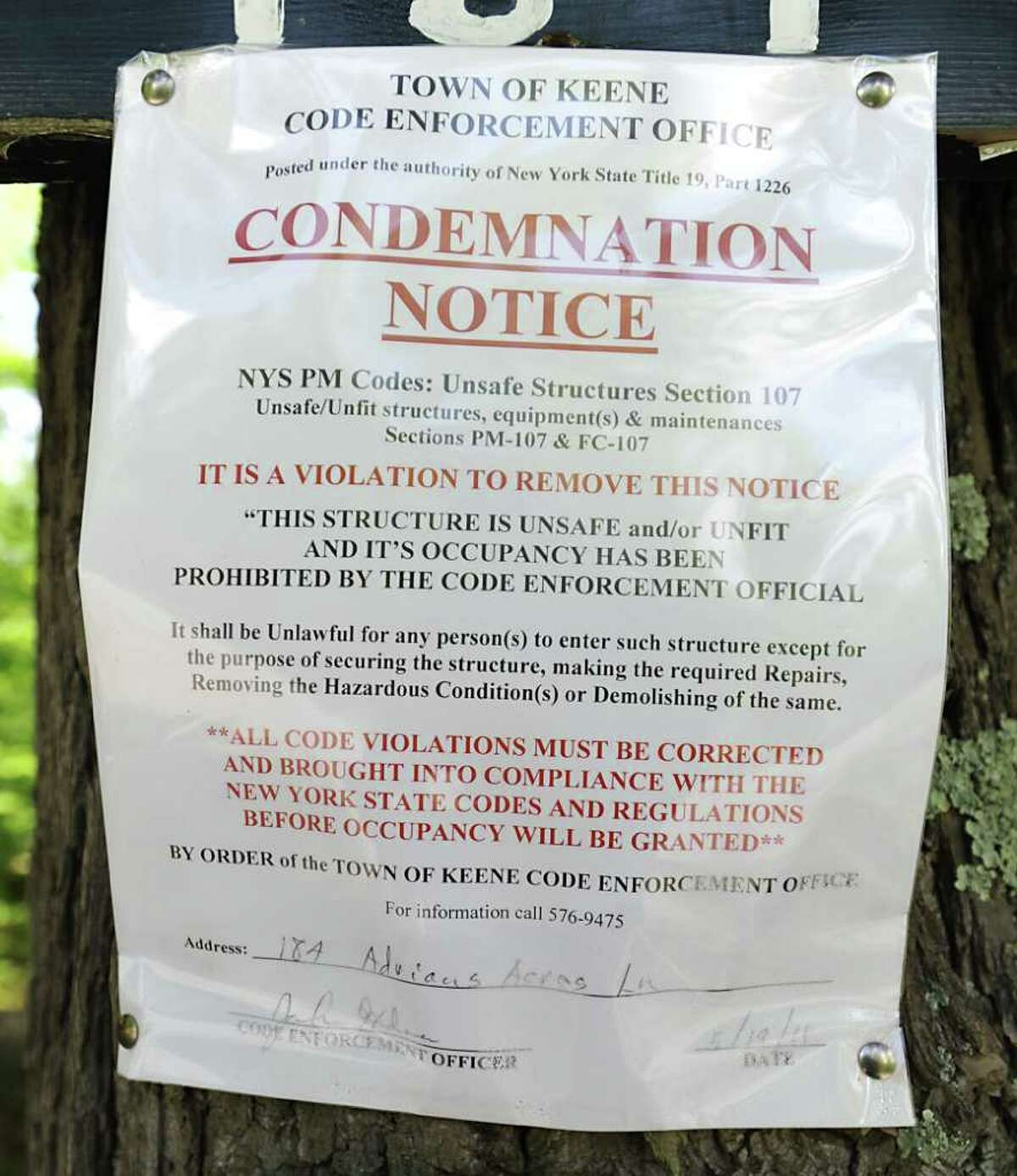 A condemnation notice is nailed to a tree at the beginning of the Machold's driveway in Keene Valley, N.Y. Tuesday May 31, 2011. (Lori Van Buren / Times Union)