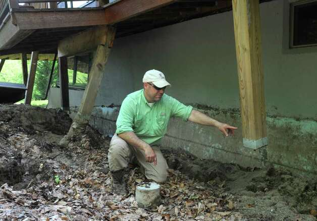Geologist Andy Kozlowski points to a deck post, on Pam Machold's home, that has separated from its cement foundation due to a slow landslide in Keene Valley, N.Y. Tuesday May 31, 2011. (Lori Van Buren / Times Union) Photo: Lori Van Buren