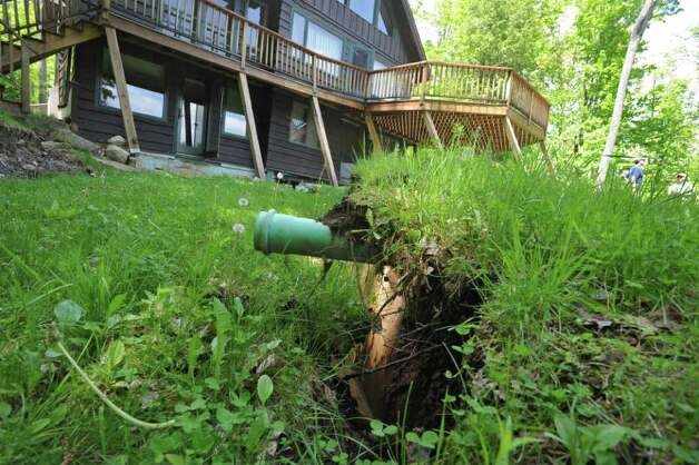 An underground pipe is exposed, at Pam Machold's home, due to a slow landslide in Keene Valley, N.Y. Tuesday May 31, 2011. (Lori Van Buren / Times Union) Photo: Lori Van Buren