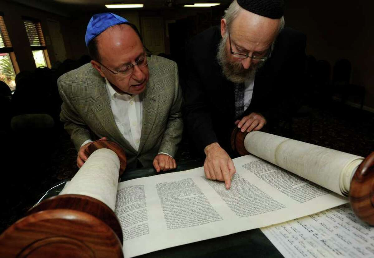 Mel Indyk, left, and Rabbi Chaim Block read through one of two Torah scrolls at Chabad Lubavitch of San Antonio on Wednesday, June 1, 2011. Chabad Lubavitch is to receive a third Torah scroll. BILLY CALZADA / gcalzada@express-news.net abe levy story