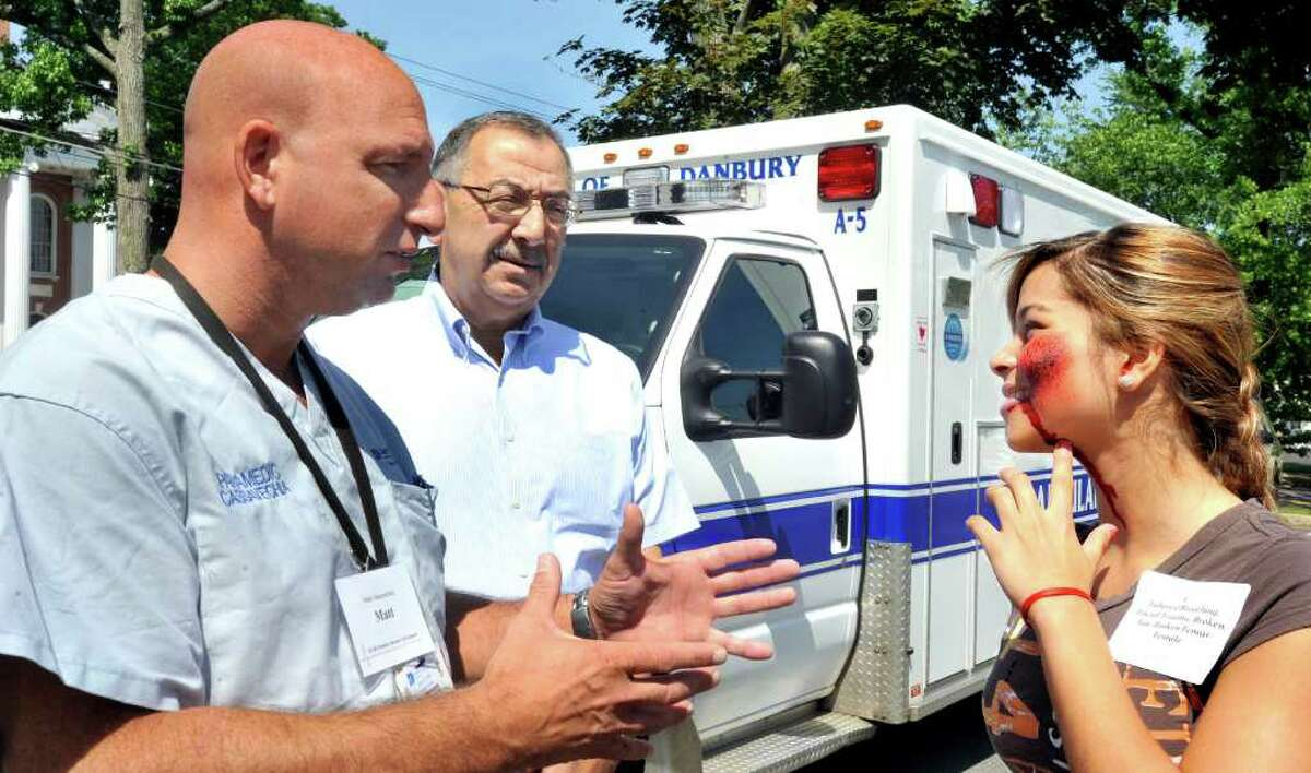 Matthew Cassavechia, director of emergency medical services for Danbury Hospital, left, and Dr. Richard Aghababian, an expert in disaster medicine, talk with Grecia Almanzar, 15, a Police Explorer volunteer playing the role of a tornado victim during a pediatric disaster life support and simulated F-4 tornado strike on a school, held at Danbury City Hall, Saturday, June 5, 2011.