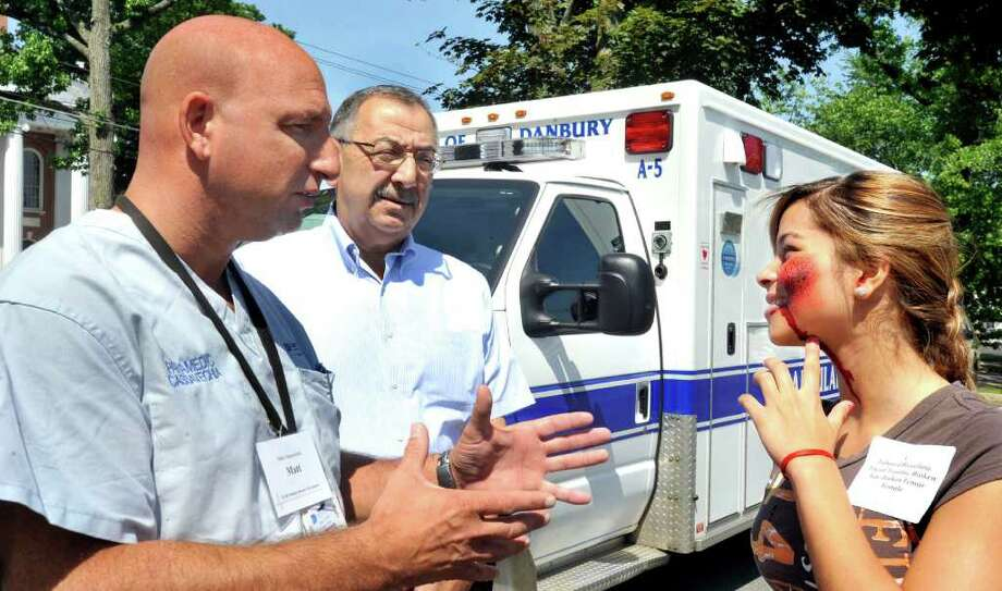 Matthew Cassavechia, director of emergency medical services for Danbury Hospital, left, and Dr. Richard Aghababian, an expert in disaster medicine, talk with Grecia Almanzar, 15, a Police Explorer volunteer playing the role of a tornado victim during a pediatric disaster life support and simulated F-4 tornado strike on a school, held at Danbury City Hall, Saturday, June 5, 2011. Photo: Michael Duffy / The News-Times