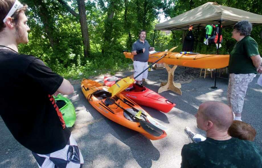 Walter Weigel, manager of Eastern Mountain Sports at the Danbury Fair mall, center, gives a talk on kayaks at the Still River Greenway Day event on Corporate Drive in Danbury. Saturday, June 4, 2011. Photo: Scott Mullin / The News-Times Freelance