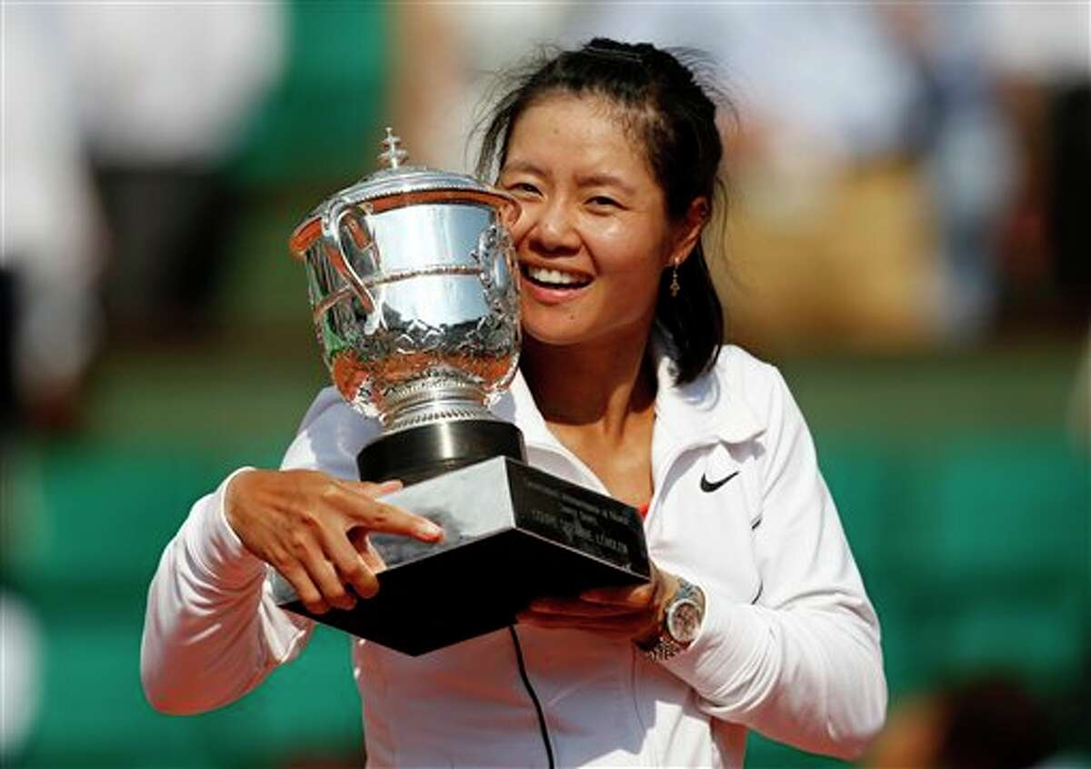 China's Li Na holds the cup after defeating Italy's Francesca Schiavone during their women's final match for the French Open tennis tournament at the Roland Garros stadium, Saturday June 4, 2011 in Paris. Li Na won 6-4, 7-6.. (AP Photo/Christophe Ena)