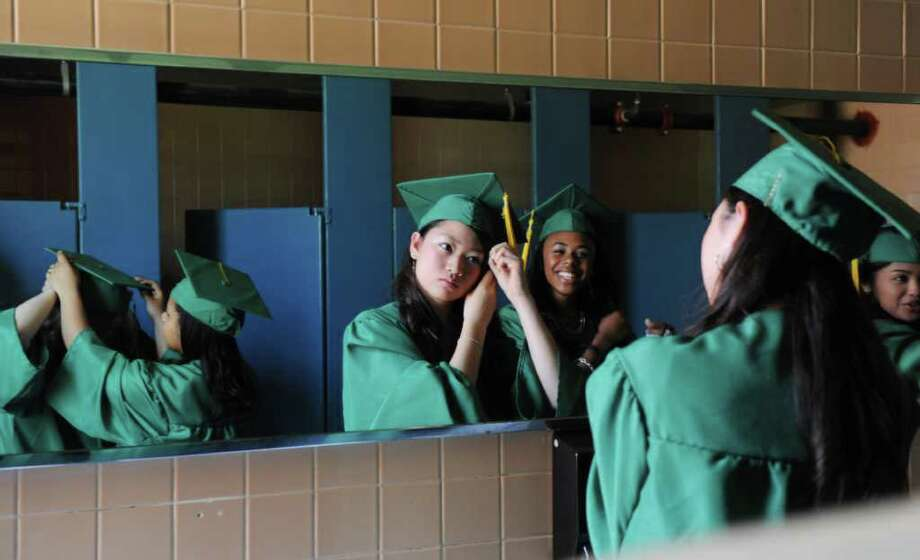 An Sakai and Jahlae Gudger put the final touches on their caps before the Trinity Catholic High School Class of 2011 Commencement Exercises in Stamford, Conn. on Saturday June 4, 2011. Photo: Kathleen O'Rourke / Stamford Advocate
