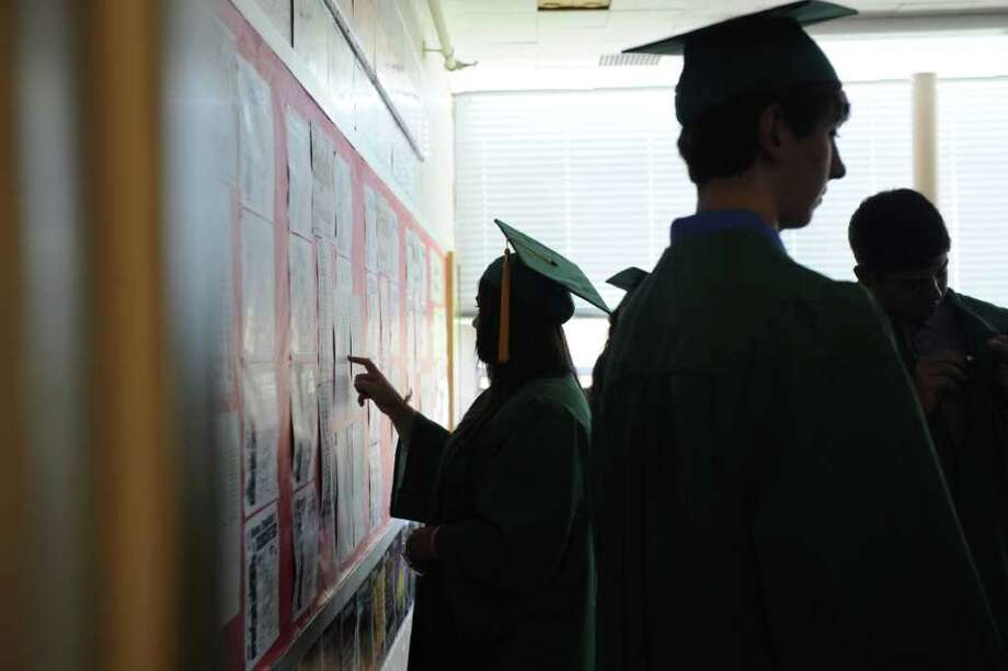 Members of the Trinity Catholic High School Class of 2011 check out their final grades before participating in the Commencement Exercises in Stamford, Conn. on Saturday June 4, 2011. Photo: Kathleen O'Rourke / Stamford Advocate