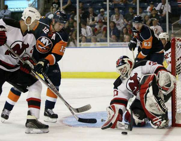 BRIDGEPORT, CT - SEPTEMBER 29: Martin Brodeur #30 of the New Jersey Devils makes a stick save as his team Richard Matvichuk #24 checks Chris Simon #12 of the New York Islanders during their preseason game at the Arena at Harbor Yard on September 29, 2007 in Bridgeport, Connecticut.  (Photo by Andy Marlin/Getty Images)   *** Local Caption *** Martin Brodeur;Richard Matvichuk;Chris Simon Photo: Andy Marlin, Getty Images / 2007 Getty Images