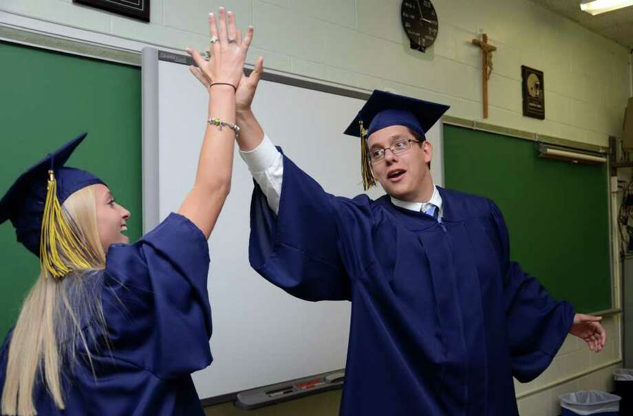 Danielle De Monte, of Bridgeport, high fives Notre Dame Class President James Weeks, of Norwalk, prior to the start of the 2011 Notre Dame Catholic High School Commencement at Notre Dame in Fairfield on Saturday, June 4, 2011. Photo: Amy Mortensen / Connecticut Post Freelance