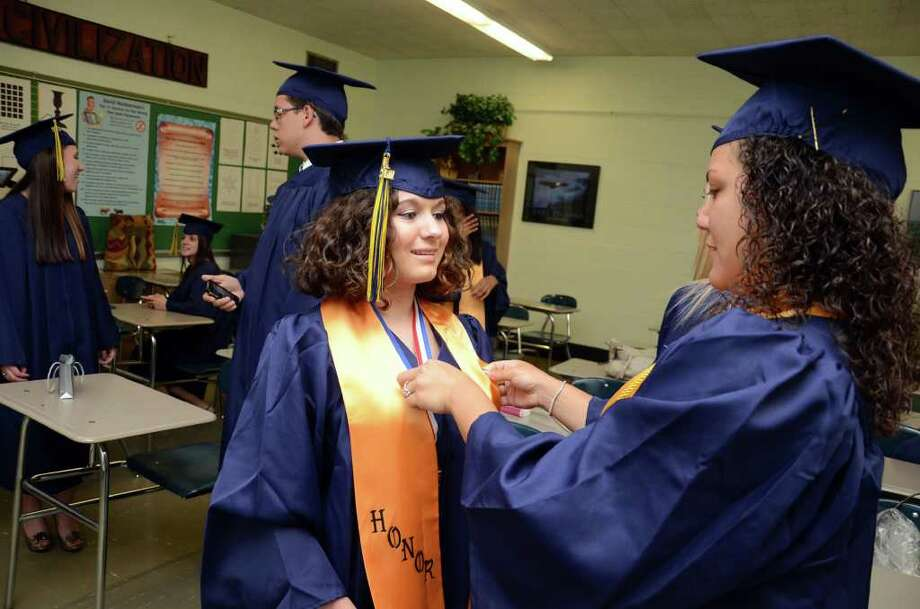 Valedictorian Jessica Harper, of Oxford, gets a little help from President of the Student Council Brittany Perez, of Bridgeport, at right, prior to the start of the 2011 Notre Dame Catholic High School Commencement at Notre Dame in Fairfield on Saturday, June 4, 2011. Photo: Amy Mortensen / Connecticut Post Freelance