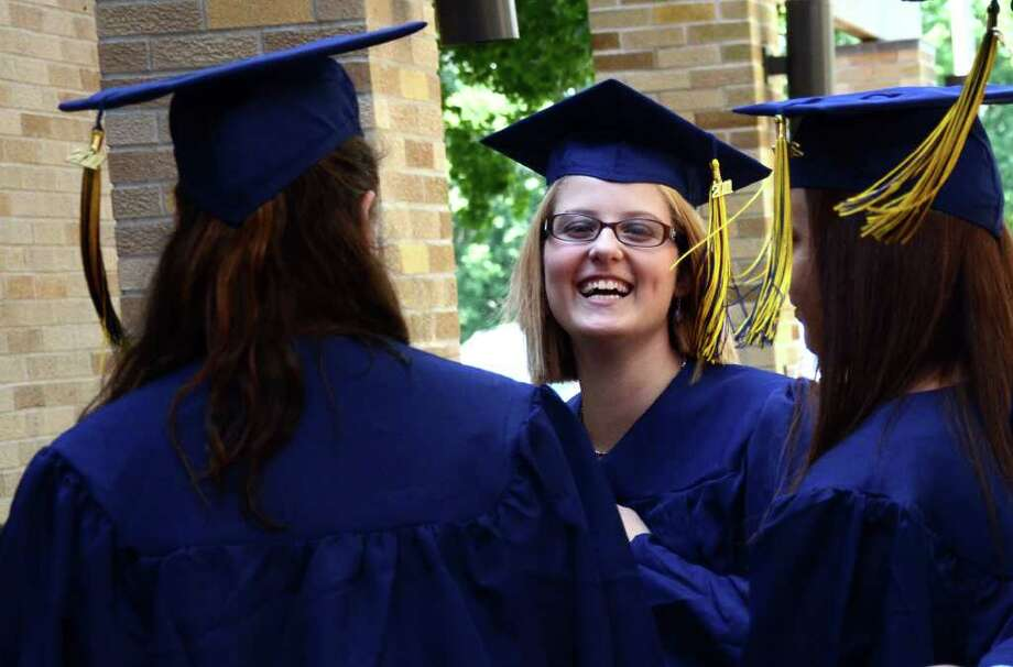 Courtney Morgan, of Shelton, center, shares a laugh with classmates Sarah Baldwin, of Bridgeport and Tracey Mauro, of Ansonia, prior to the start of the 2011 Notre Dame Catholic High School Commencement at Notre Dame in Fairfield on Saturday, June 4, 2011. Photo: Amy Mortensen / Connecticut Post Freelance