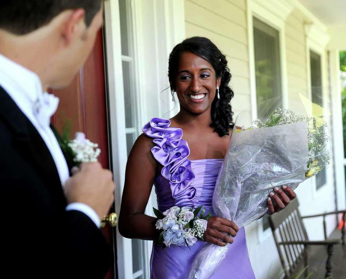 James Tate pins his boutonniere as Sonali Rodrigues holds a bouquet of flowers before they go to their senior prom on Saturday, June 4, 2011.