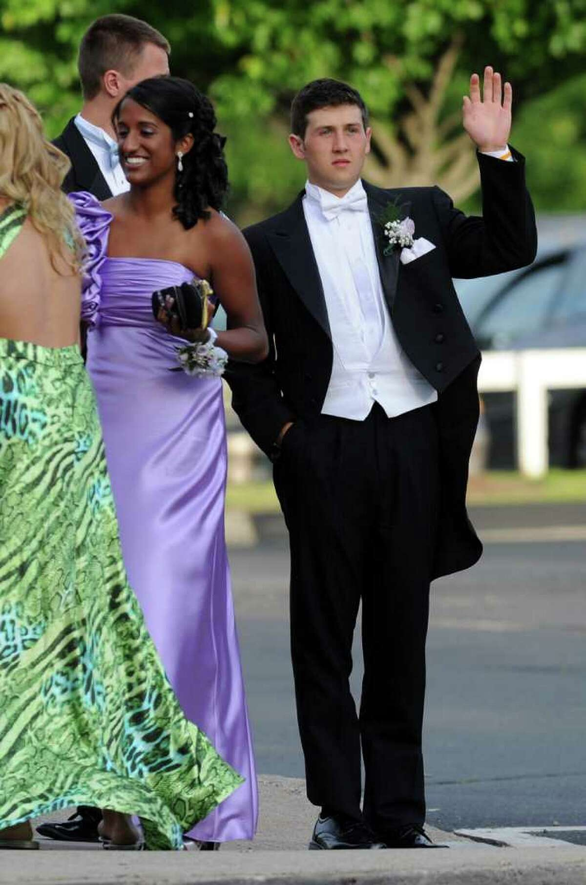 James Tate waves to the media as he and Sonali Rodrigues arrive at senior prom on Saturday, June 4, 2011. The prom was held at Oakdale Theater in Wallingford.