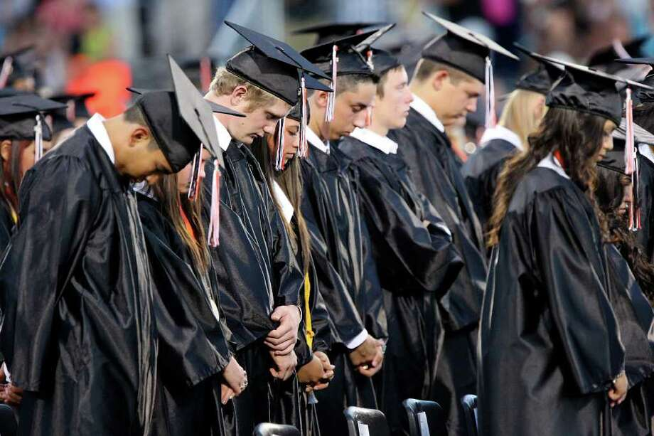 Medina Valley High School graduates pray during the Medina Valley High School graduation held Saturday June 4, 2011 at Panther Stadium in Castroville, Tx. (PHOTO BY EDWARD A. ORNELAS/eaornelas@express-news.net) Photo: EDWARD A. ORNELAS, Edward A. Ornelas/Express-News / © SAN ANTONIO EXPRESS-NEWS (NFS)