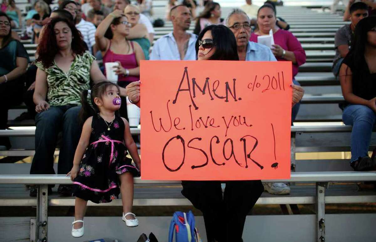 Patricia Martinez holds a sign for her nephew Oscar Guerrero Jr. as her daughter Sofia Martinez, 2, looks on during the Medina Valley High School graduation held Saturday June 4, 2011 at Panther Stadium in Castroville, Tx. (PHOTO BY EDWARD A. ORNELAS/eaornelas@express-news.net)