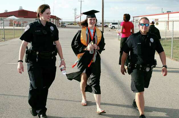 Medina Valley High School valedictorian Angela Hildenbrand (center) is escorted by law enforcement before the Medina Valley High School graduation held Saturday June 4, 2011 at Panther Stadium in Castroville, Tx. (PHOTO BY EDWARD A. ORNELAS/eaornelas@express-news.net) Photo: EDWARD A. ORNELAS, Edward A. Ornelas/Express-News / © SAN ANTONIO EXPRESS-NEWS (NFS)