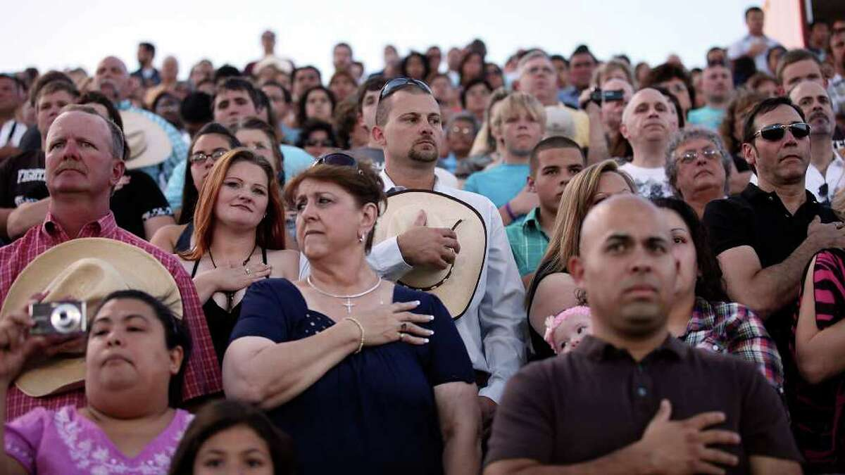 Spectators stand as Medina Valley High School valedictorian Angela Hildenbrand (not pictured) sings the national anthem during graduation held Saturday June 4, 2011 at Panther Stadium in Castroville, Tx. (PHOTO BY EDWARD A. ORNELAS/eaornelas@express-news.net)