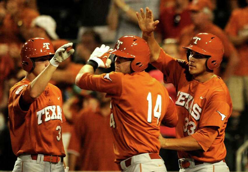 Kevin Lusson (14) is met by teammates Paul Montalbano, left, and Jonathan Walsh after hitting a ninth-inning home run during NCAA Baseball Austin Regional action against Kent State on Saturday, June 4, 2011. BILLY CALZADA / gcalzada@express-news.net