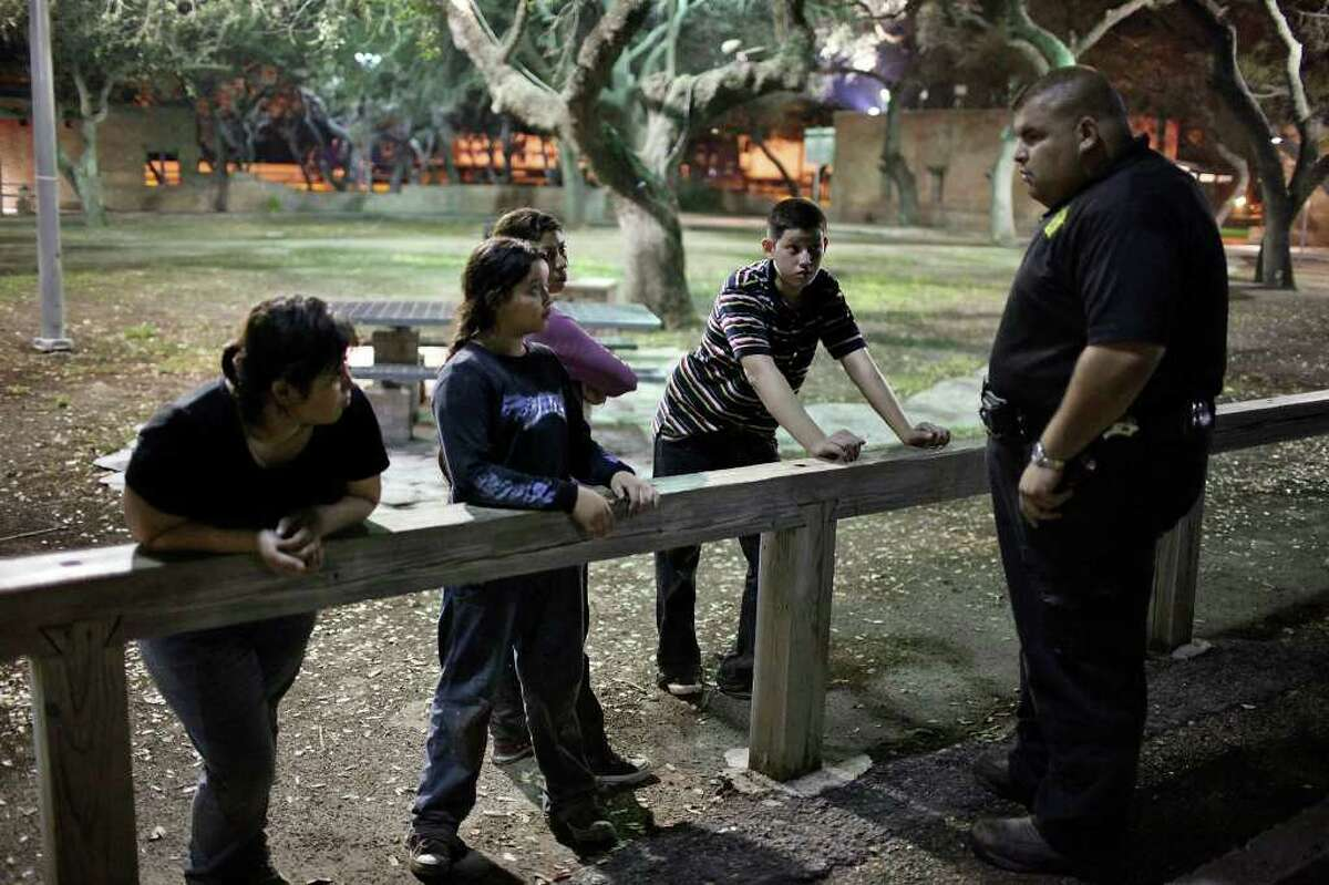 Brooks County Sheriff Department deputy Modesto Saavedra III (right) questions undocumented immigrants from El Salvador Sandra Marlena Cortillo (from left) her daughter Alizo, 10, sister Anna, and son Bryan, 13, Friday May 20, 2011 at a rest area near Falfurrias, Tx. (PHOTO BY EDWARD A. ORNELAS/eaornelas@express-news.net)