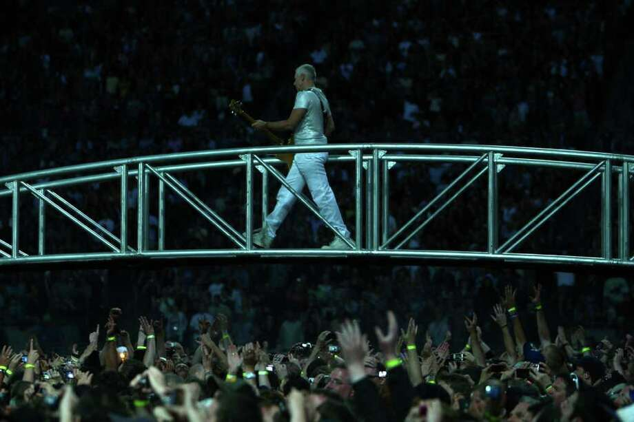U2 bassist Adam Clayton performs on a bridge over the crowd. Photo: JOSHUA TRUJILLO / SEATTLEPI.COM