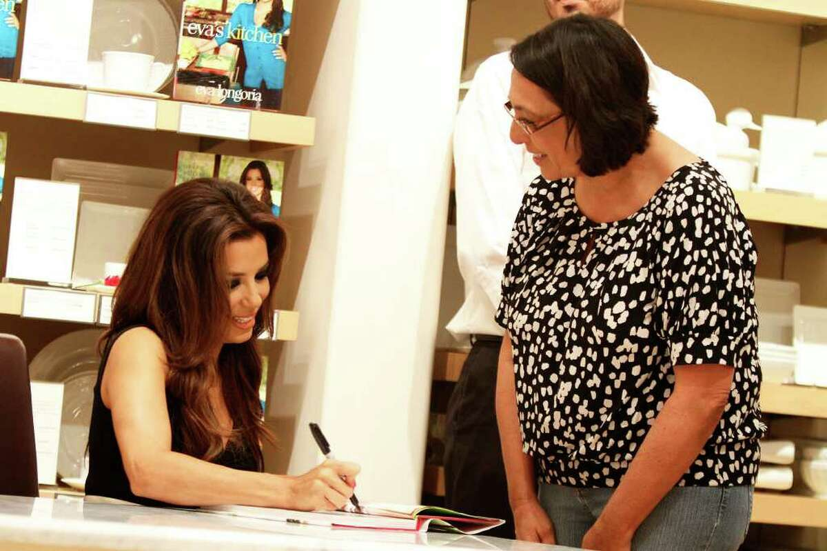 Eva Longoria signs a book for Corpus Christi resident Mary Clary during a book signing for her first cookbook,