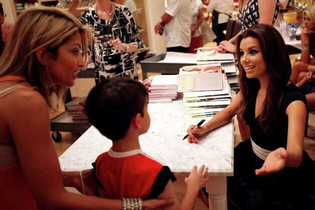 "Eva Longoria, right, greets customers at a signing event for her first cookbook, ""Eva's Kitchen: Cooking with Love for Family and Friends"", June 4, 2011, at Williams-Sonoma at the Shops at La Cantera. Only people with on of 400 tickets were allowed to get Longoria's signature in their books.   ANDREW BUCKLEY / abuckley@express-news.net Photo: ANDREW BUCKLEY, Andrew Buckley/Express-News / SAN ANTONIO EXPRESS-NEWS"