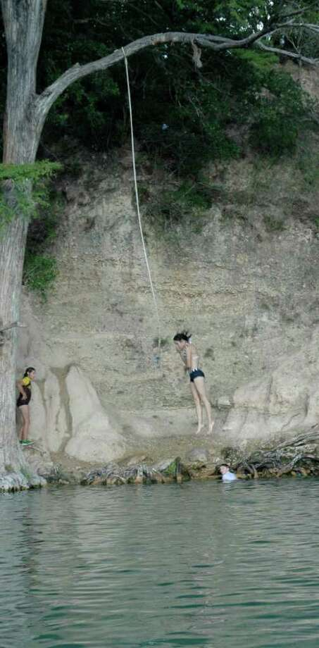 Youngsters swinging out over the Frio River water and let go at Garner State Park. Photo: Express-News File Photo
