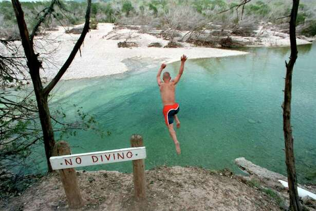 Micheal Gorney, 17, of Cypress, jumps off a deteriorating Frio river bank wall at Garner State Park on Wednesday, March 17, 1999.