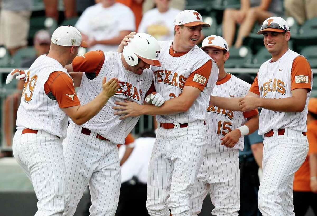 Texas' Kevin Lusson (left center) is congratulated by teammates after making a hit to score the winning run against Texas State during the ninth inning of the 2011 NCAA Baseball Austin Regional held Sunday June 5, 2011 at Disch-Falk Field in Austin Tx. Texas won 4-3.
