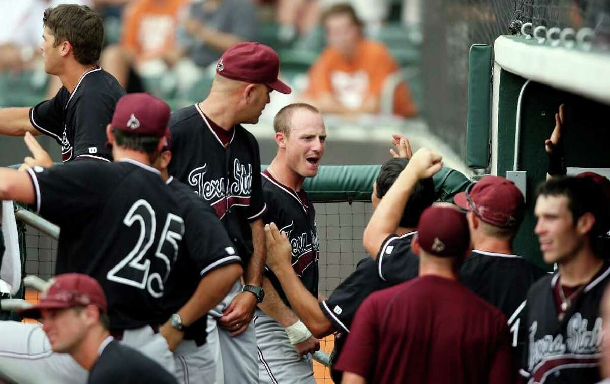 Texas State's Bret Atwood (center) celebrates with teammates after scoring against Texas during the ninth inning.