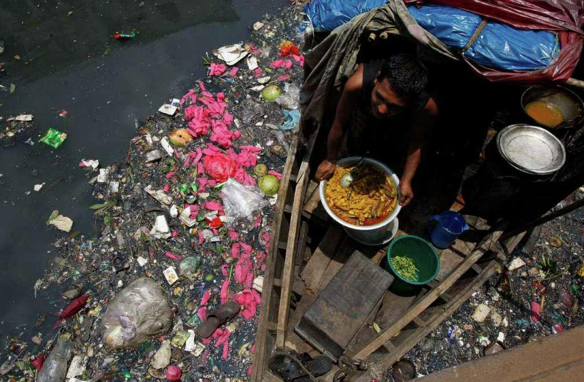 A boatman prepares food in his boat on the polluted river Buriganga in Dhaka, Bangladesh, Sunday, June 5, 2011. World Environment Day is celebrated June 5 every year by the United Nations to stimulate worldwide awareness of environmental issues and encourages political action.