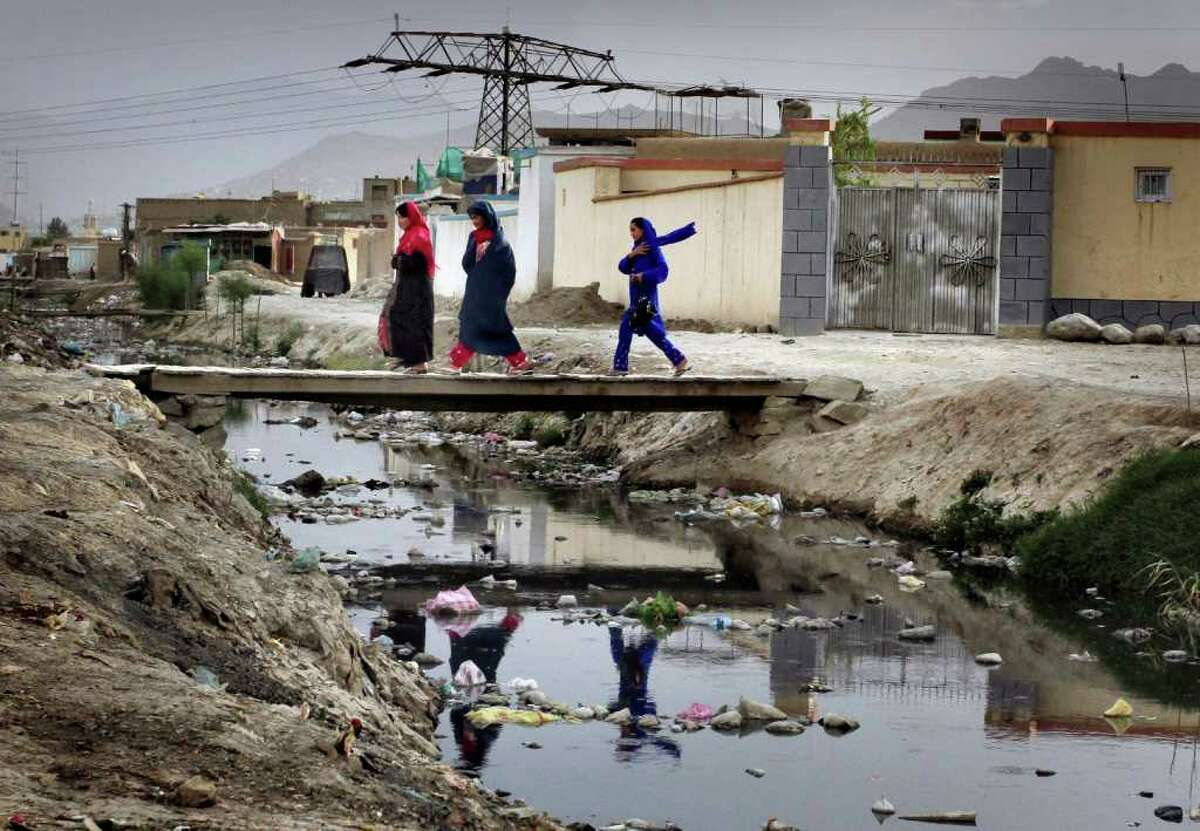 Afghans walk over a walking bridge, placed on flood water on the World Environment Day in Kabul, Afghanistan on Sunday, June 5, 2011.
