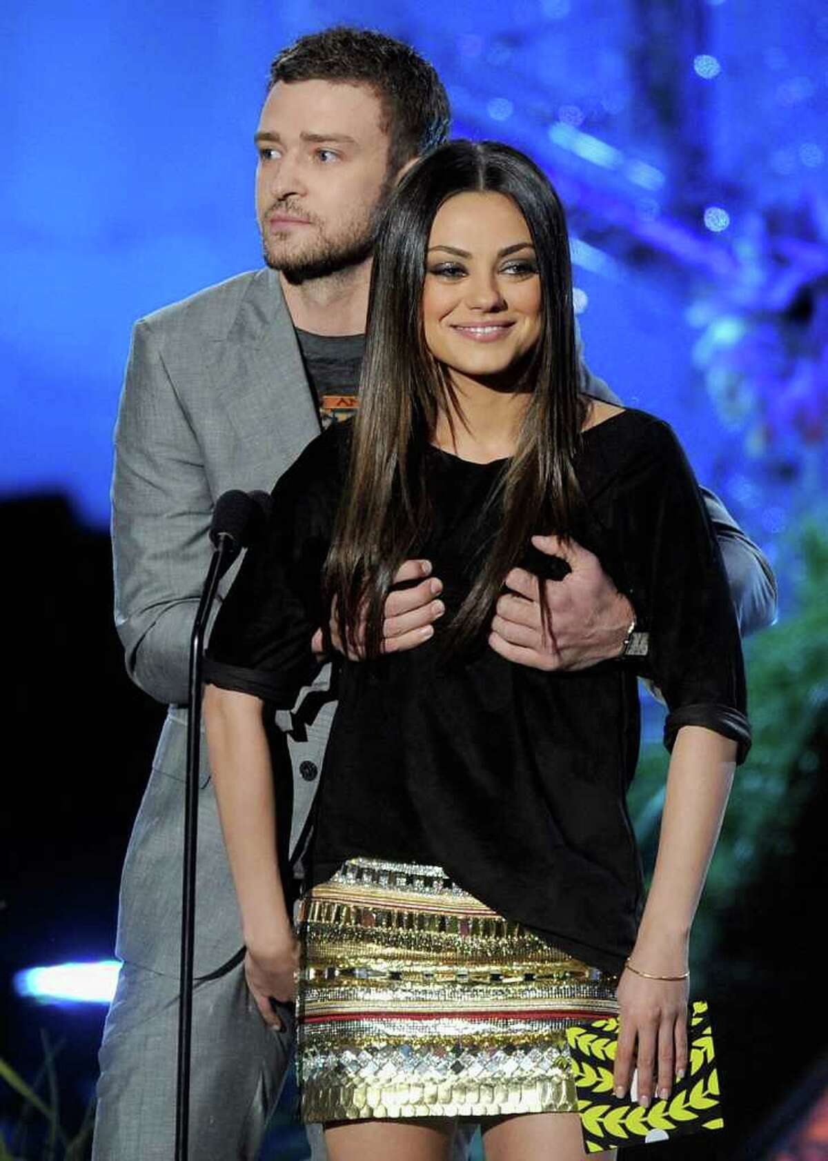 Actors Justin Timberlake (L) and Mila Kunis present an award onstage.