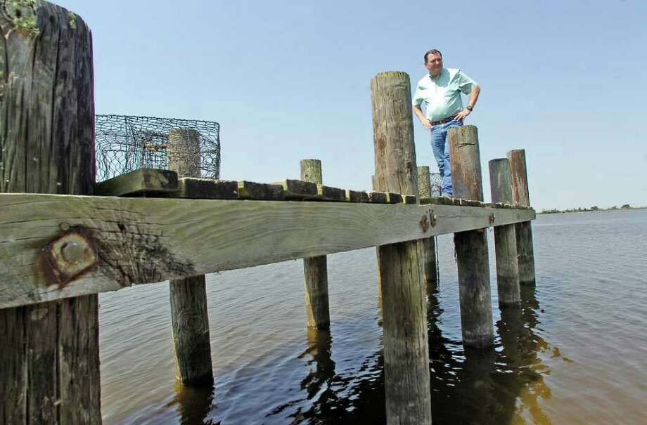Steve Edwards walks along a pier next to a boat ramp looking at the water level in one of the stocked ponds on land his family owns near Winnie.  The water, prior to the ongoing drought, normally would be up to the bottom of the side plank attached to the pilings   It is at such a low point right now that water is being pumped in from Elm Bayou to bring the level up in the bass pond.  Dave Ryan/The Enterprise Photo: Dave Ryan
