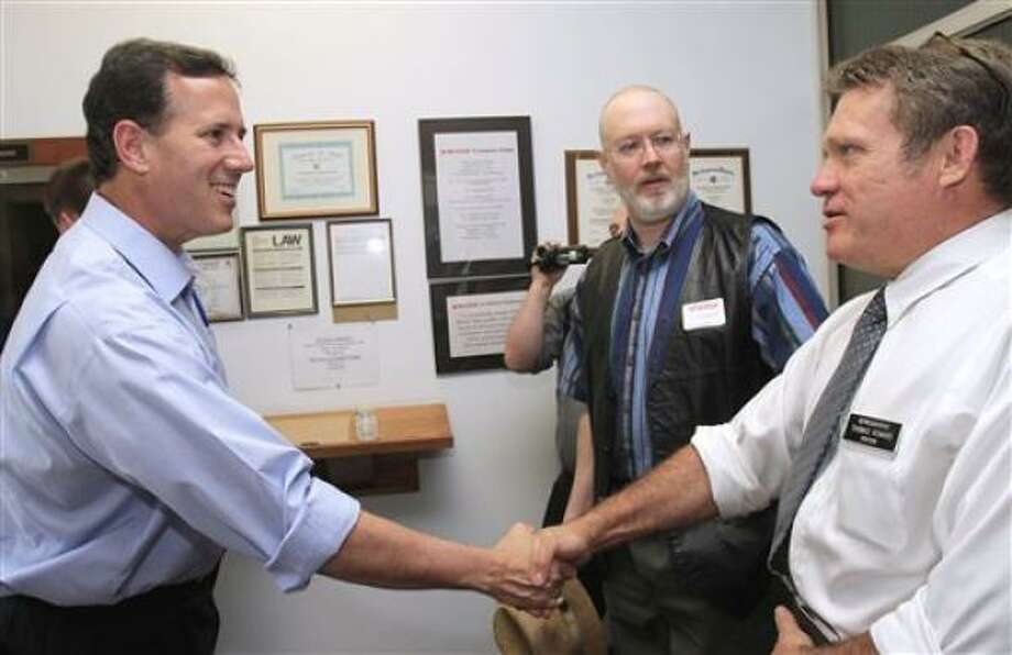 FILE - In this May 31, 2011, file photo former Pennsylvania Sen. Rick Santorum shakes hands with New Hampshire state Rep. Thomas Howard before touring Rugar Firearms in Newport, N.H.  Santorum is set to formally announce on Monday, June 6, 2011, he is seeking the Republican party's presidential nomination. (AP Photo/Jim Cole) Photo: Jim Cole, AP